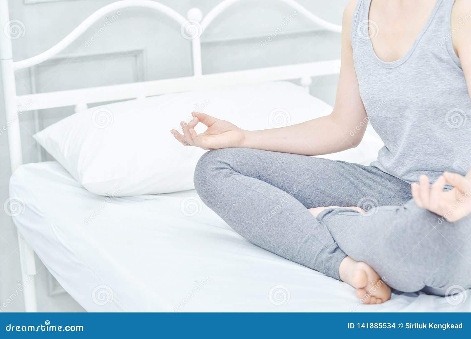 Mädchen tragen graue Hemden und die Hosen und sitzen auf Yoga auf der Matratze