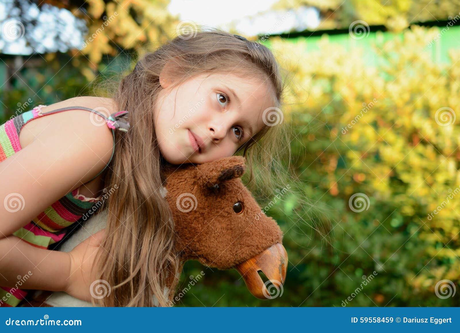 Mädchen umarmt ein Schaukelpferd