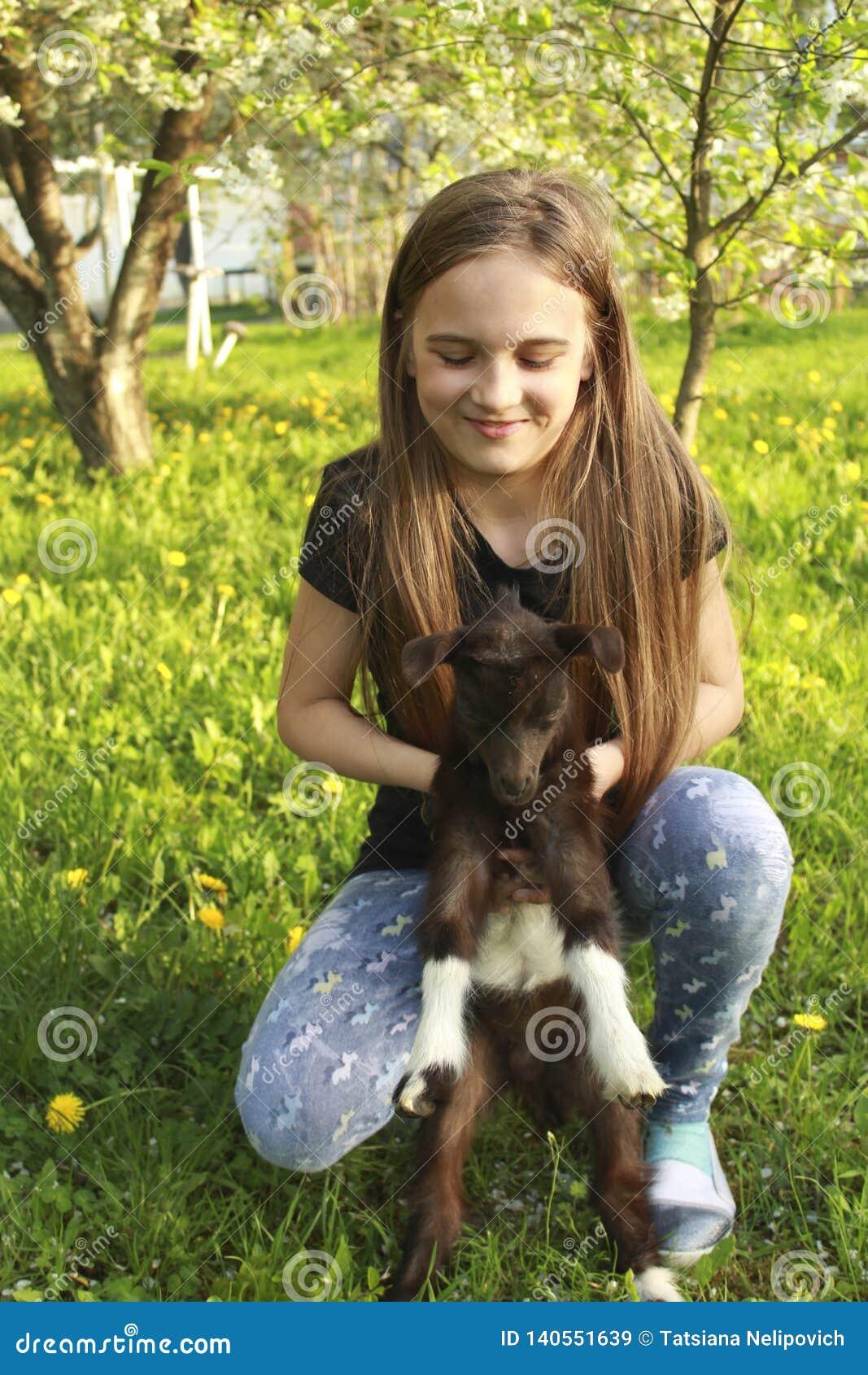 Mädchen- und Babyziege in geblühtem Garten