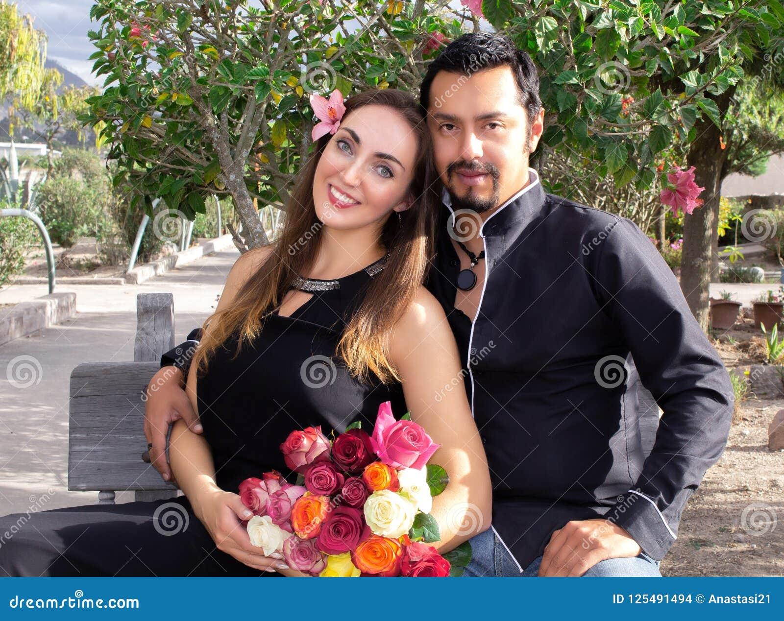 Mädchen und Junge küssen im Garten Ein Mann und eine Frau umarmen das Sitzen auf einer Bank in der Natur in einem blühenden Garte