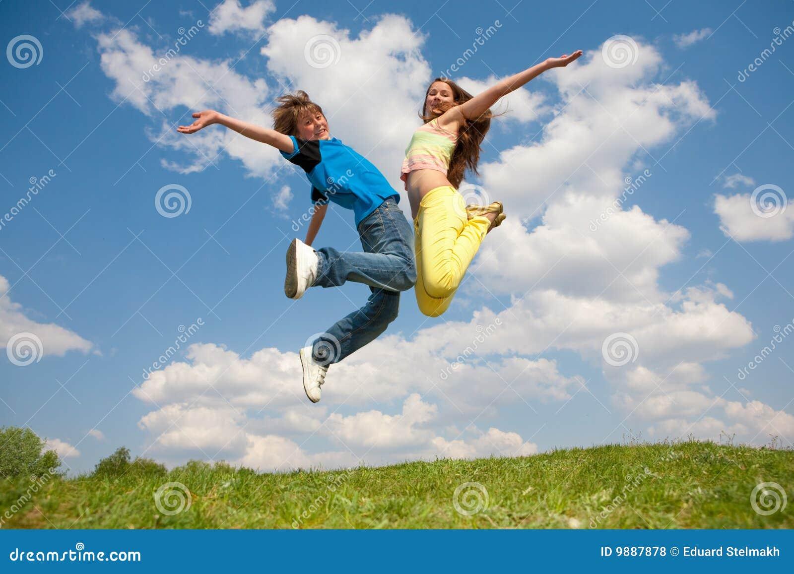 Mädchen und Junge - springend unter Himmel