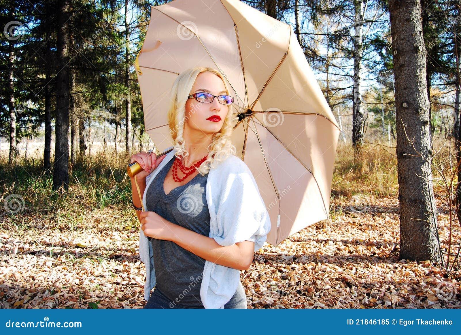 Mädchen unter Regenschirm im Herbstwald.
