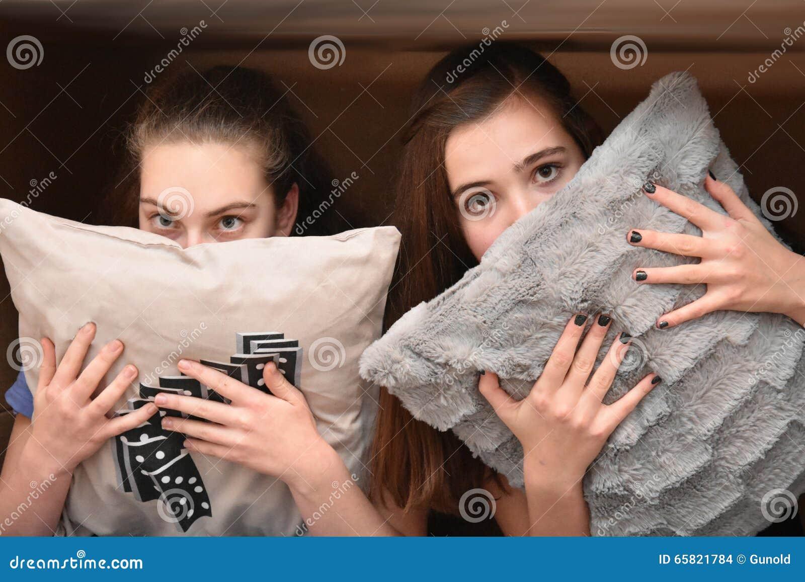 Mädchen versteckt hinter einem Kissen