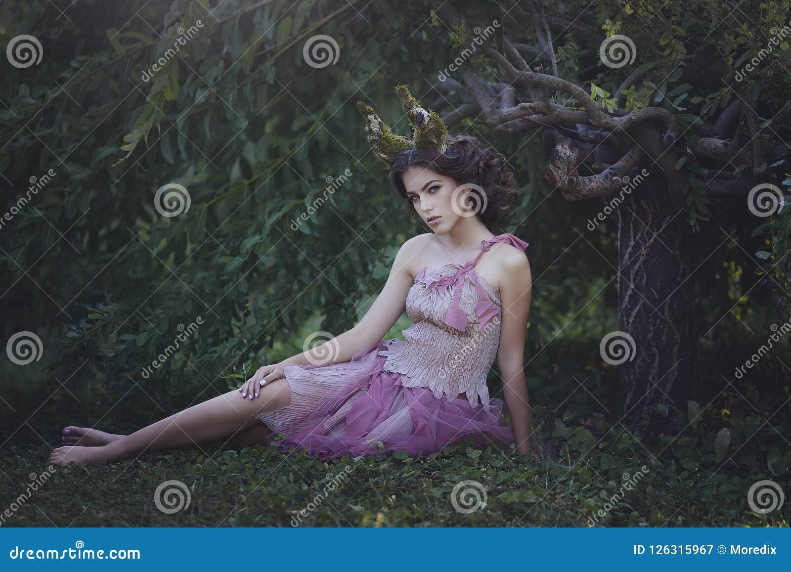 Mädchen verzauberte Prinzessin mit den Hörnern, die unter einem Baum sitzen Mystisches Geschöpfkitz des Mädchens in der schäbigen