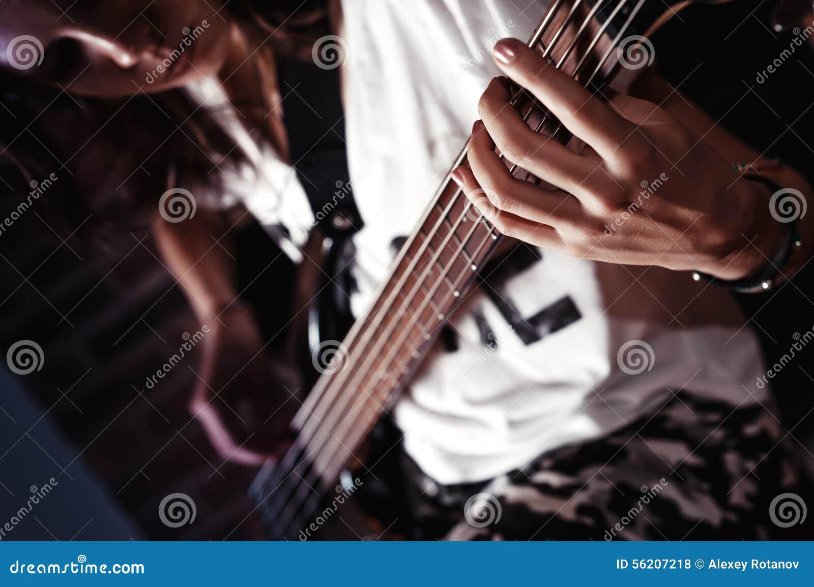 Mädchen, welches die Bass-Gitarre Innen in der Dunkelkammer spielt