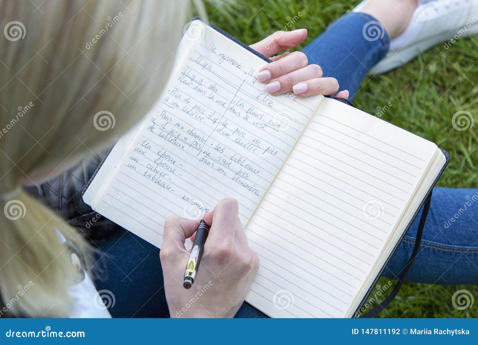 Mädchenarbeiten schreibt Informationen in ein Notizbuch