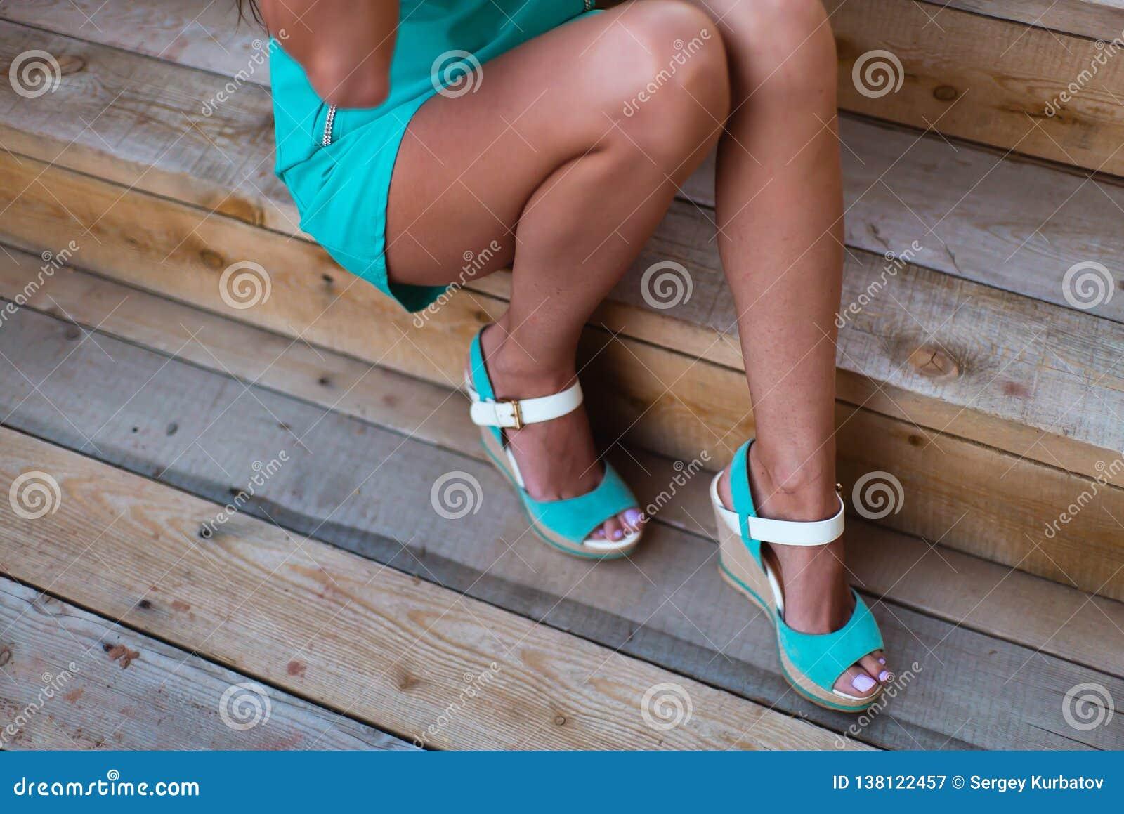 Mädchenbeine im Türkiskurzschlusskleid, das auf einem Baumklotz sitzt