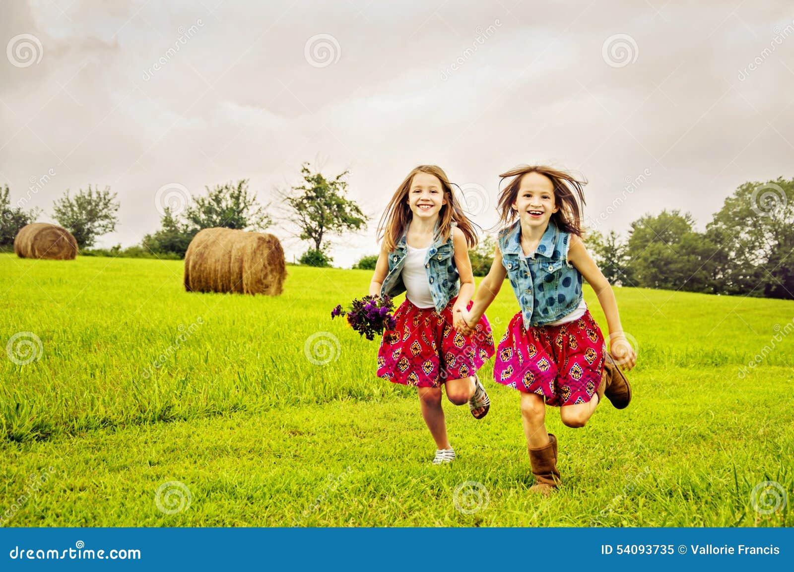 Mädchengeschwister, die in Weide laufen