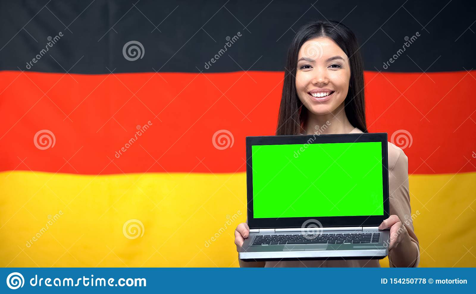 Mädchenholdinglaptop mit grünem Schirm, deutsche Flagge auf dem Hintergrund, reisend