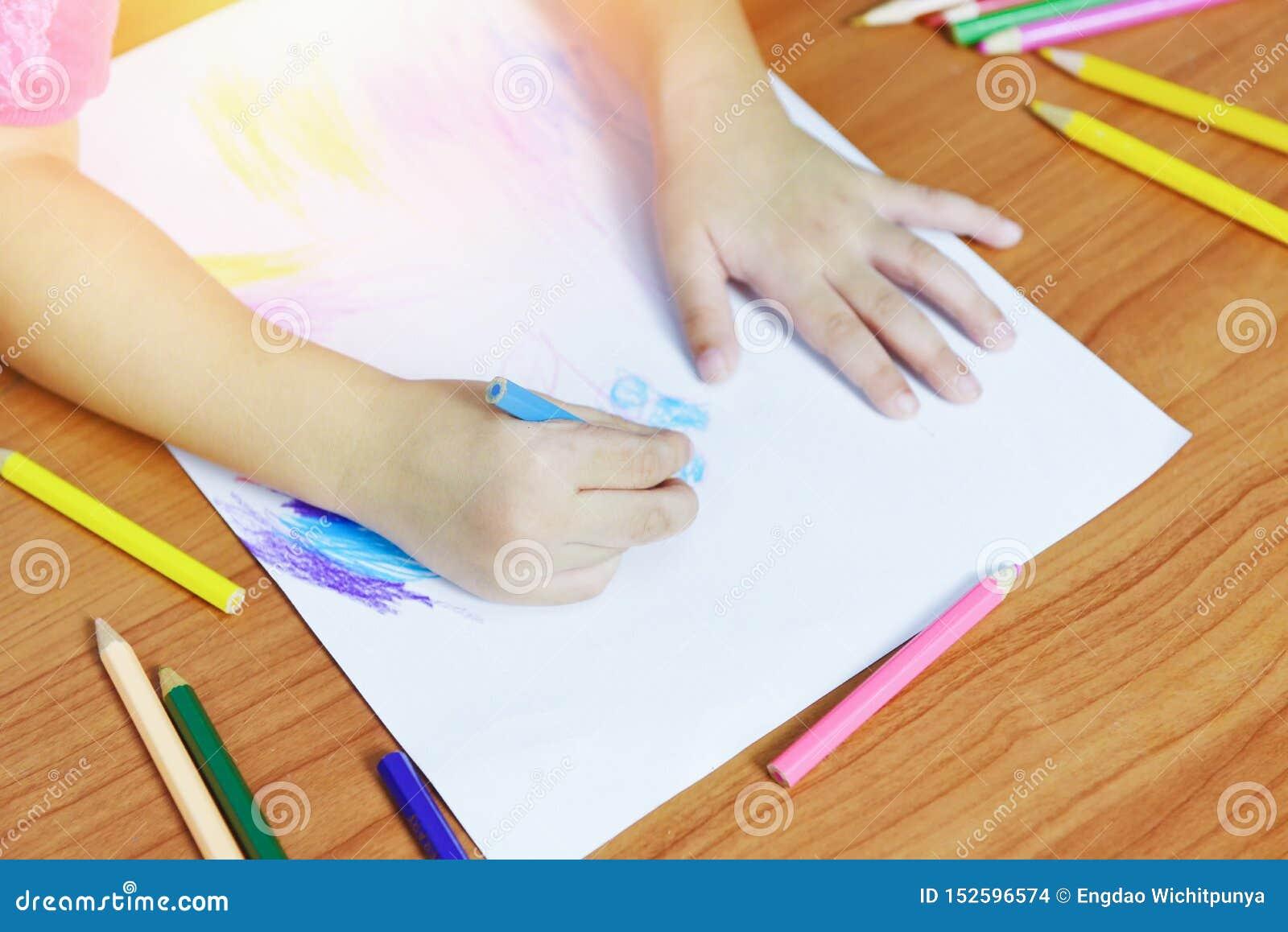 Mädchenmalerei auf Papierblatt mit Farbbleistiften auf dem Kind des Holztischs zu Hause - Kinder, daszeichnendes Bild und bunten