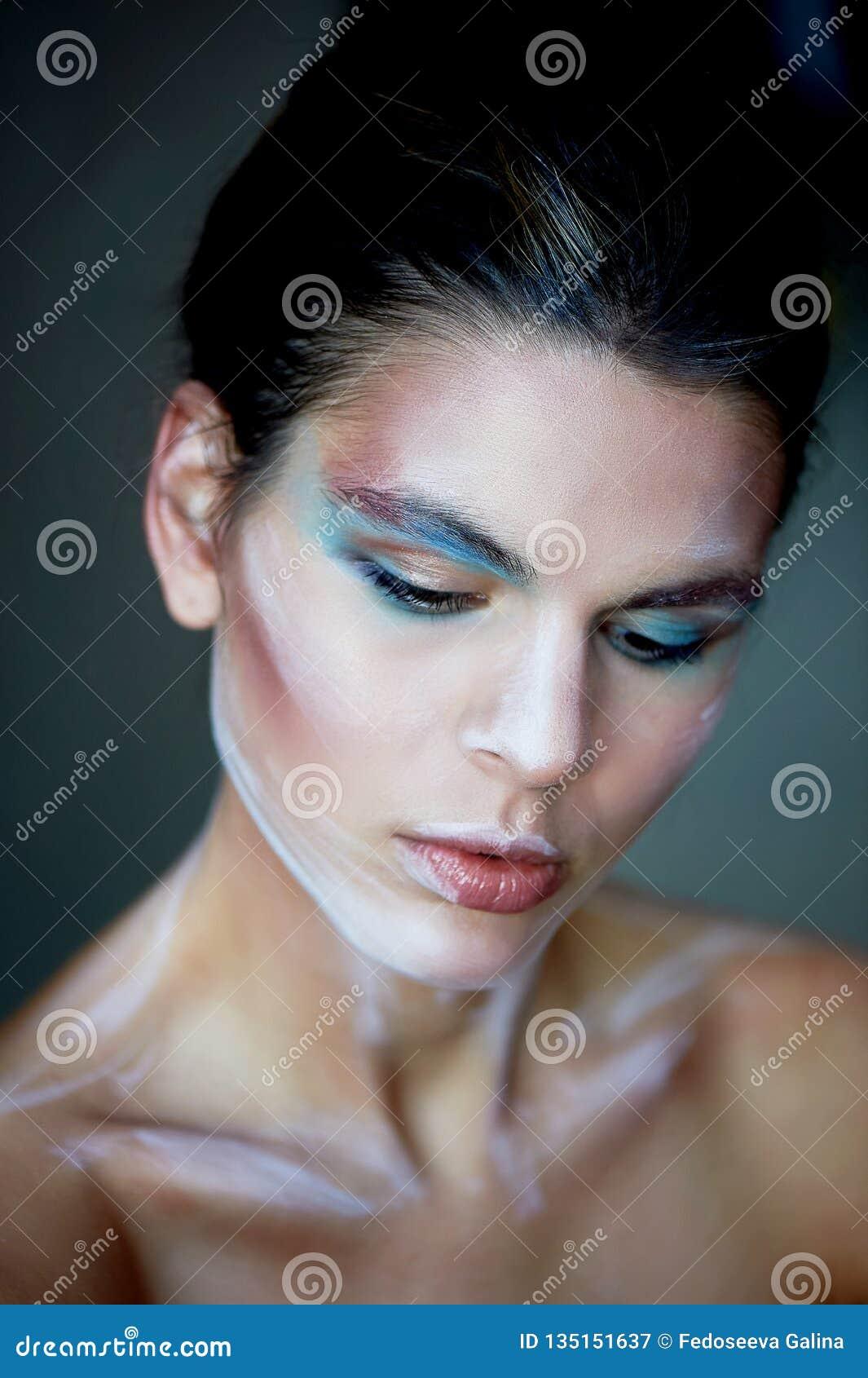 Mädchenmodell mit kreativem Make-up, Farbenanschläge auf dem Gesicht Kreative Person Lebende Skulptur Schauen Sie unten