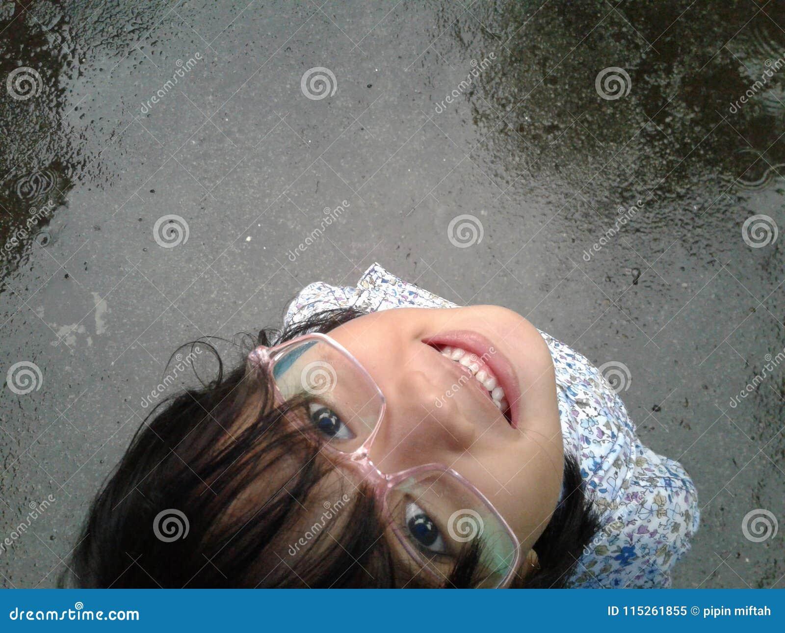 Mädchenstand auf nasser Straße
