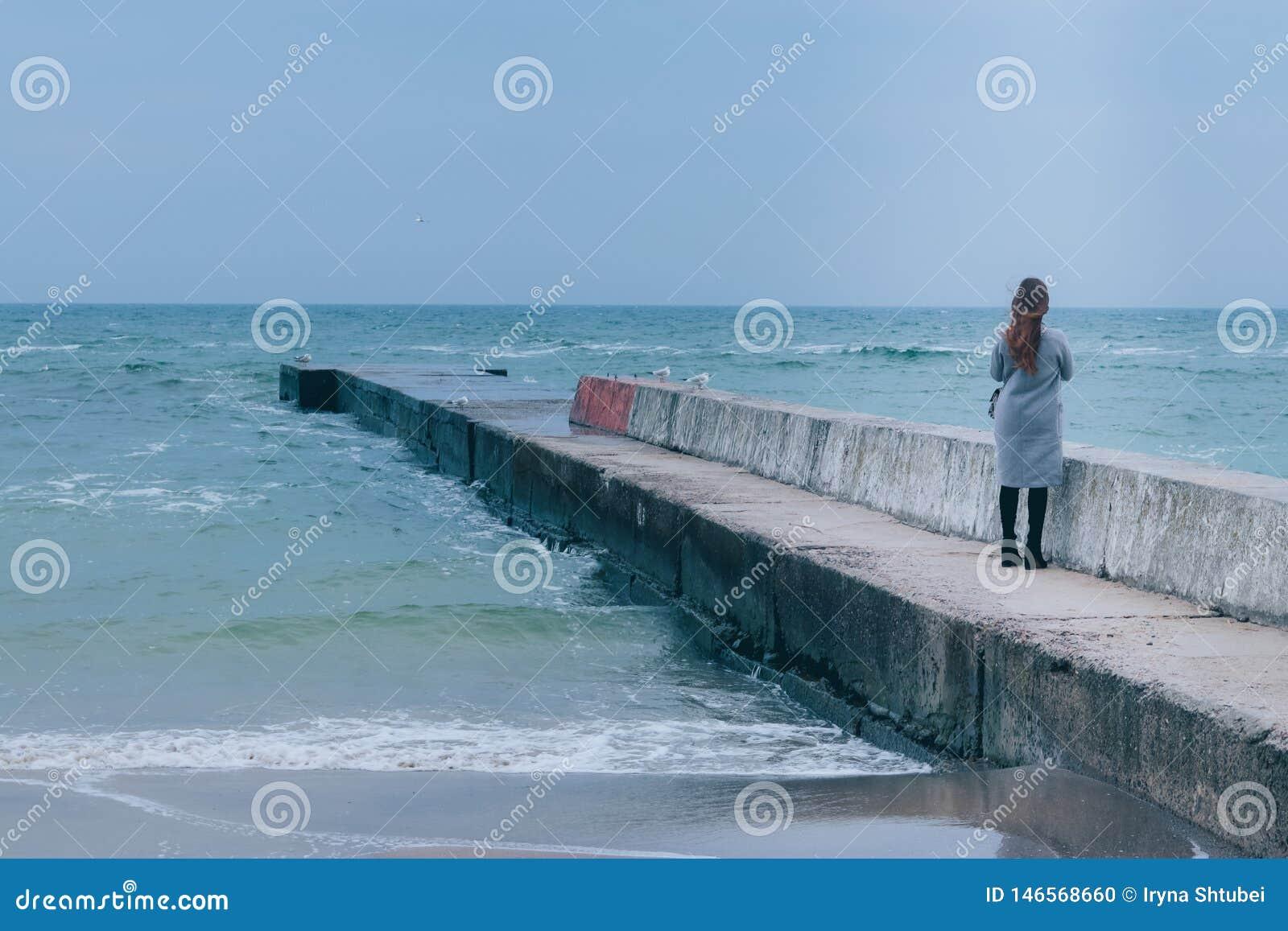 Mädchenstellung auf dem Seepier in der kalten Jahreszeit