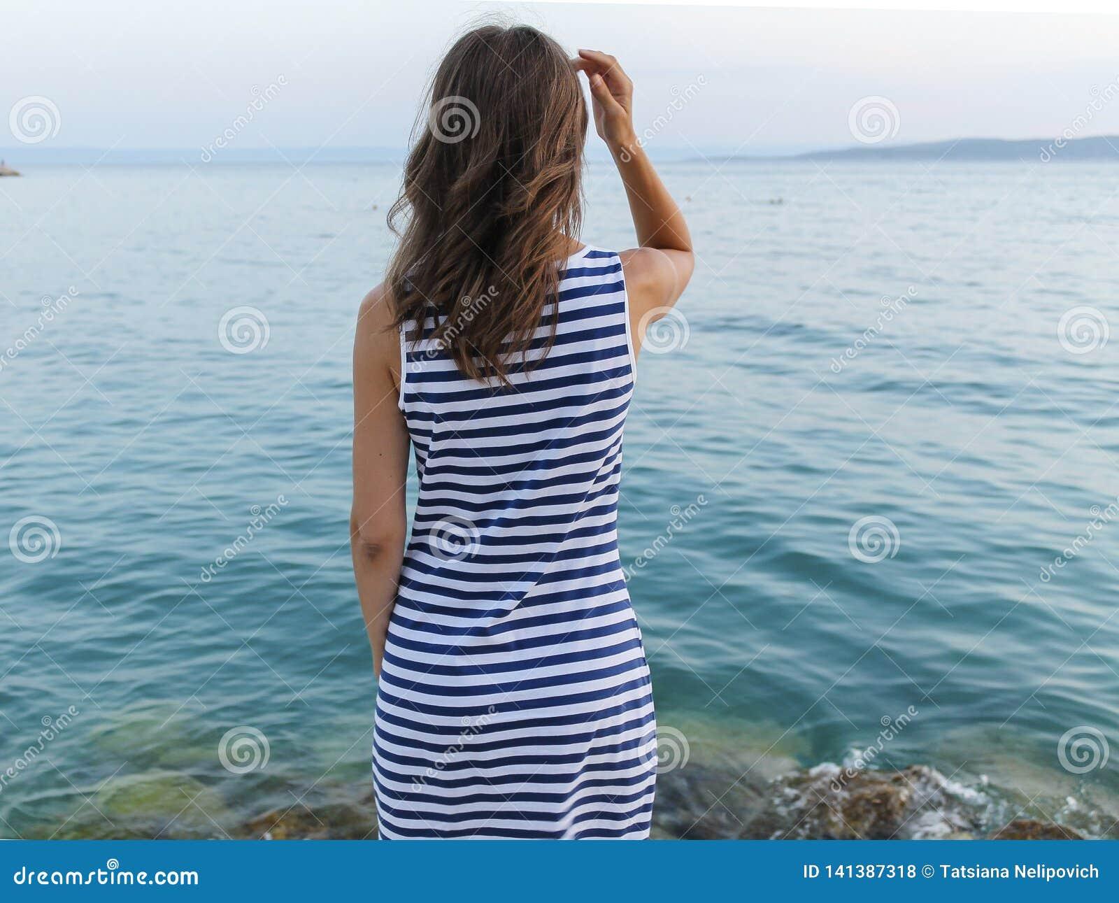 Mädchenstellung auf Ufer und Betrachten von Meer