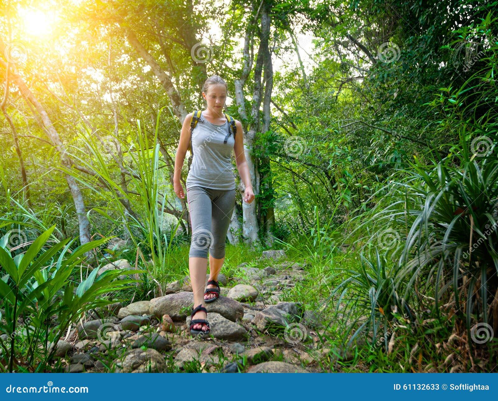 Mädchentourist mit einem Rucksack gehend entlang die Spur im jung