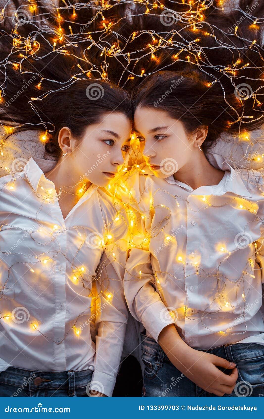 Mädchenzwillinge mit Lichtern Neues Jahr ` s Eve Weihnachten Gemütlicher Feiertag am Tannenbaum mit Lichtern und Golddekor
