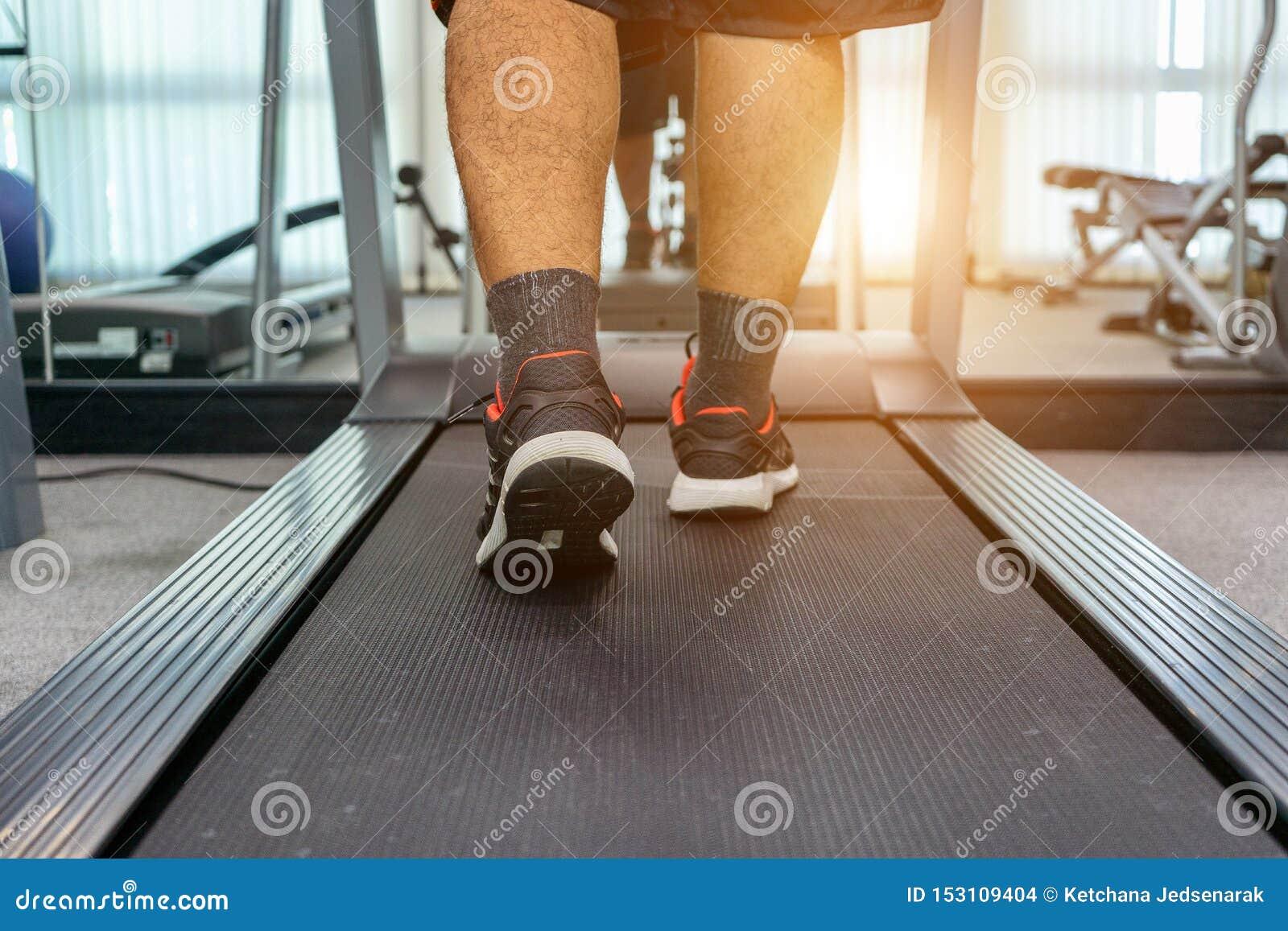 Män övar, genom att köra på en trampkvarn, når de har arbetat i en inomhus konditionmitt för aktivitet som en sund kropp Begrepps