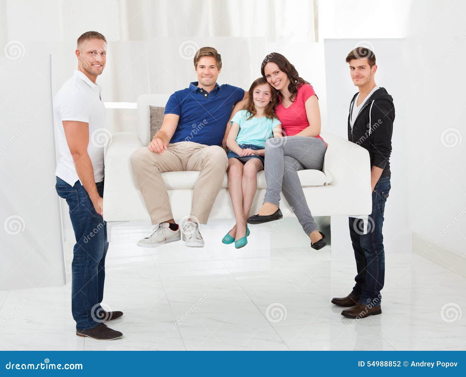 Män som bär soffan med en familj
