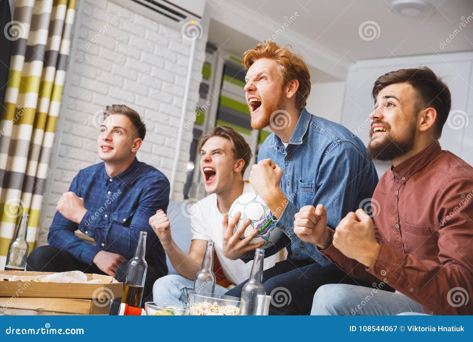 Män som tillsammans håller ögonen på sporten på att ropa för tv som hemma är lyckligt