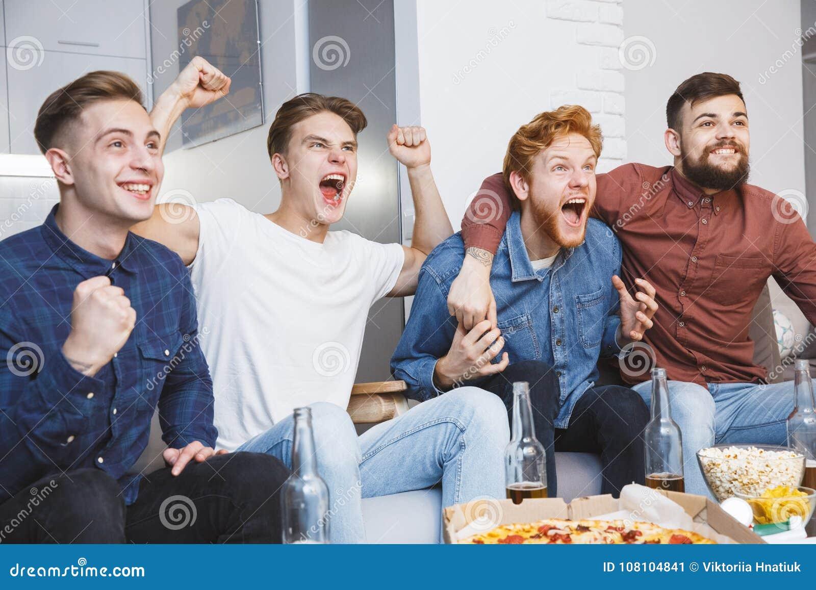 Män som tillsammans håller ögonen på sporten på att skrika för tv som hemma är gladlynt