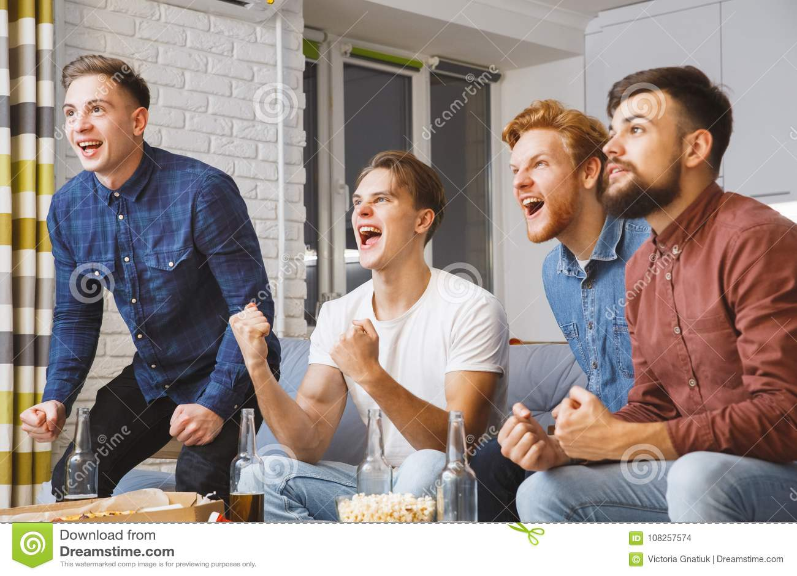 Män som tillsammans håller ögonen på sporten på det segrade hemmastadda laget för tv