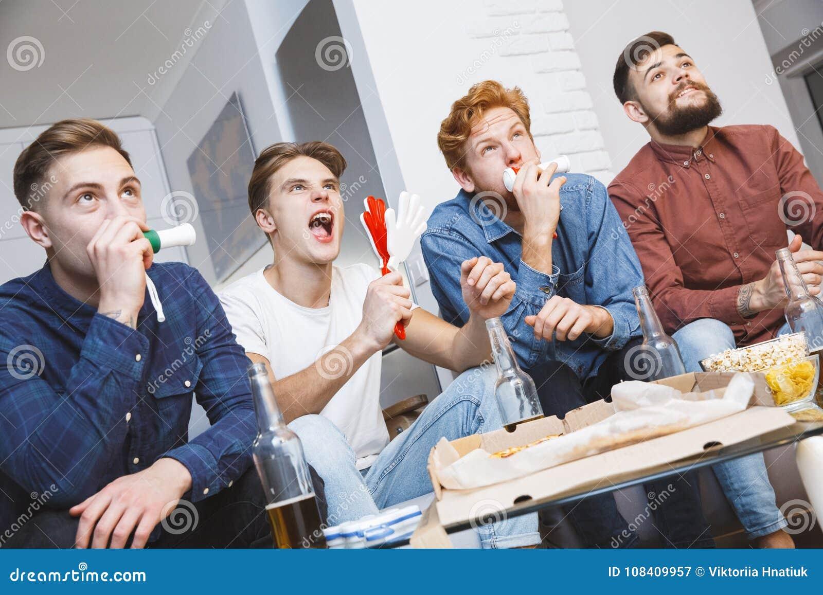 Män som tillsammans håller ögonen på sporten på för lagande för tv hemmastatt bifall
