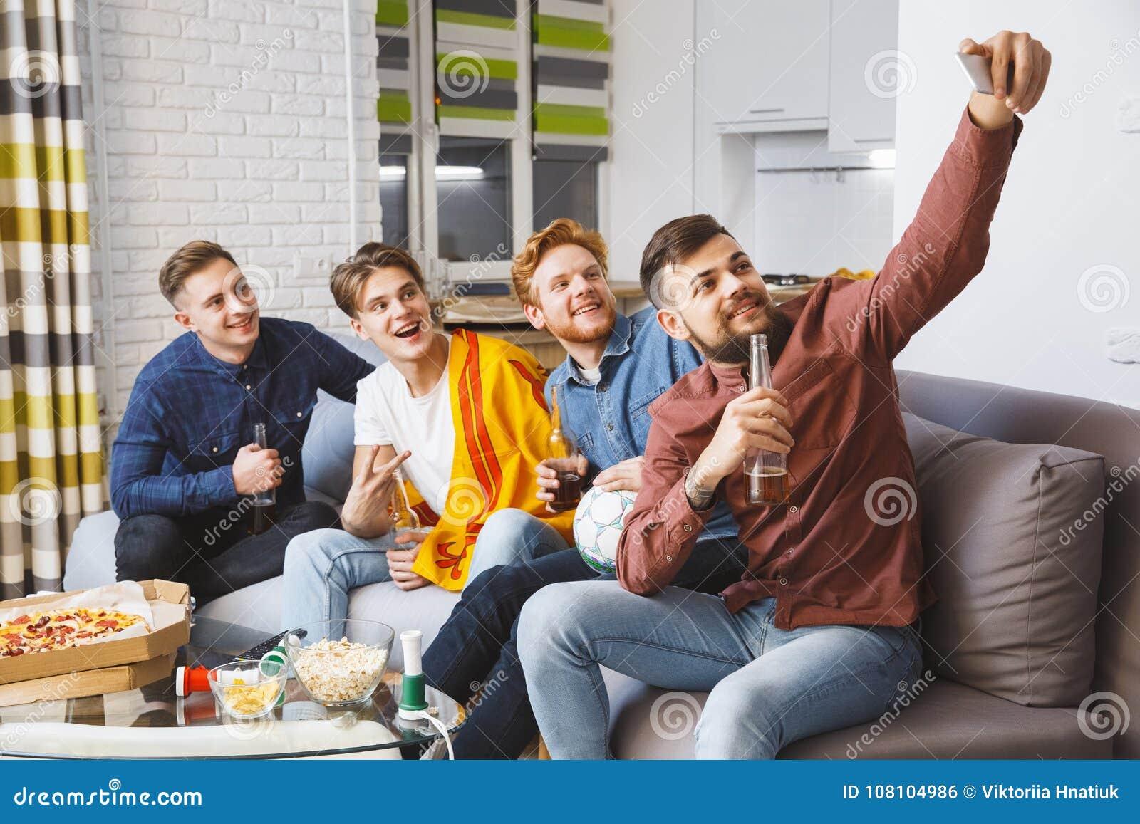 Män som tillsammans håller ögonen på sporten på hemmastadda selfiebilder för tv