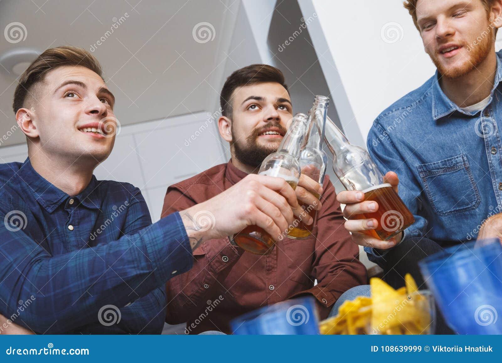 Män som tillsammans håller ögonen på sporten på hemmastatt rostat bröd för tv för lagnärbild