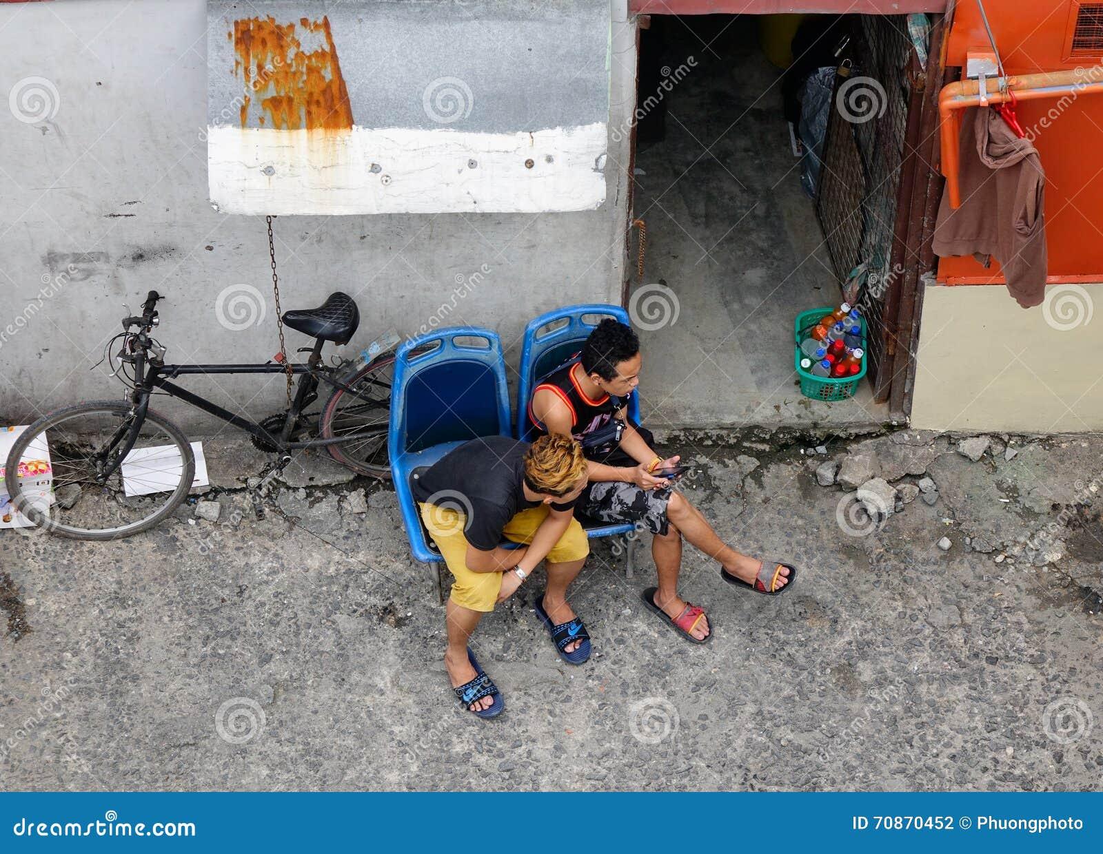 Männer, die auf Straße in Manila, Philippinen sitzen