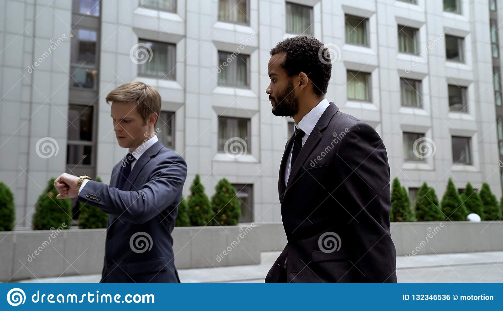 Männer, die zum wichtigen Geschäftstreffen, Uhr betrachtend, Zeitmanagement gehen
