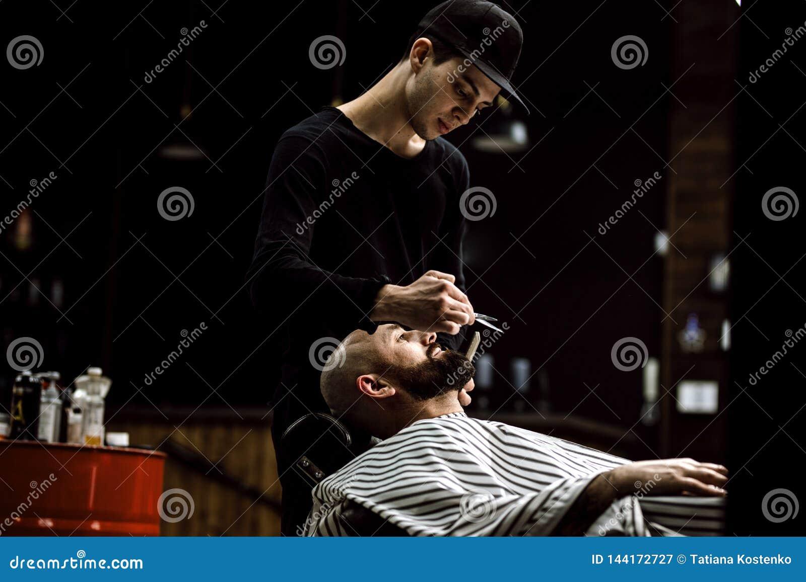 Männer ` s Art Der Friseur kleidete in schwarze Kleidung, die Scheren vom groben Mann im stilvollen Friseursalon trotzen