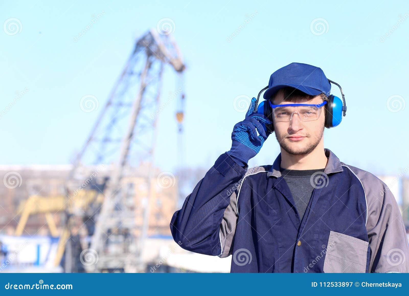 Männliche Arbeitskraft mit Kopfhörern draußen