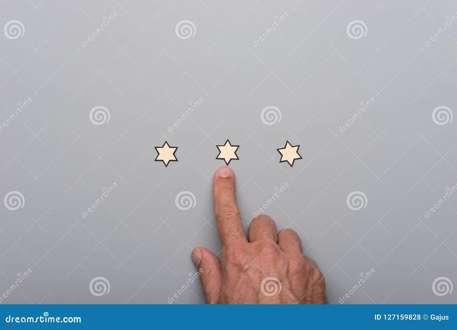 Männliche Hand, die auf an von drei Papierschnittsternen zeigt
