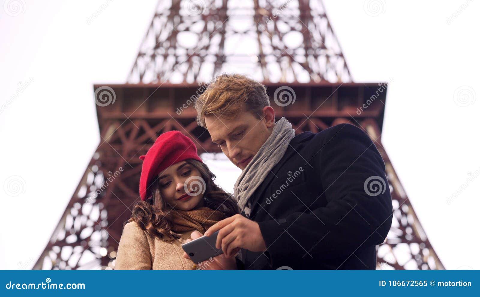 Männliche und weibliche Touristen, die Bestimmungsort in Paris auf Karte in beweglicher APP suchen