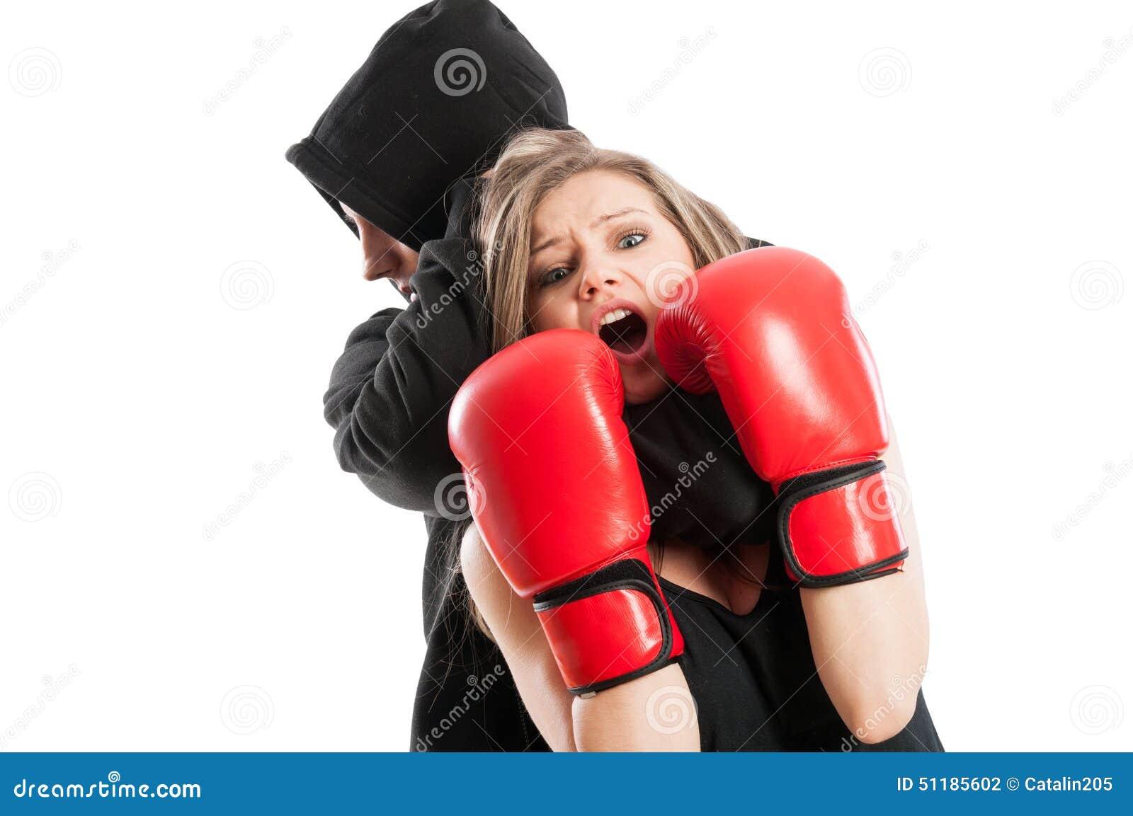 Männlicher Angreifer Ergreifungstragende Boxhandschuhe einer erschrockene Frau