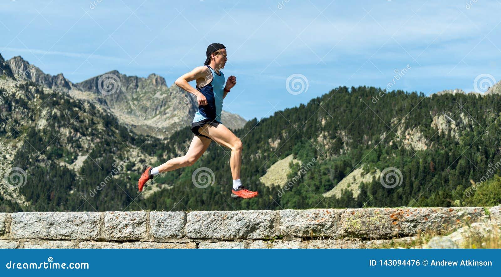 Männlicher Athlet, der über eine Steinwand in den Bergen läuft