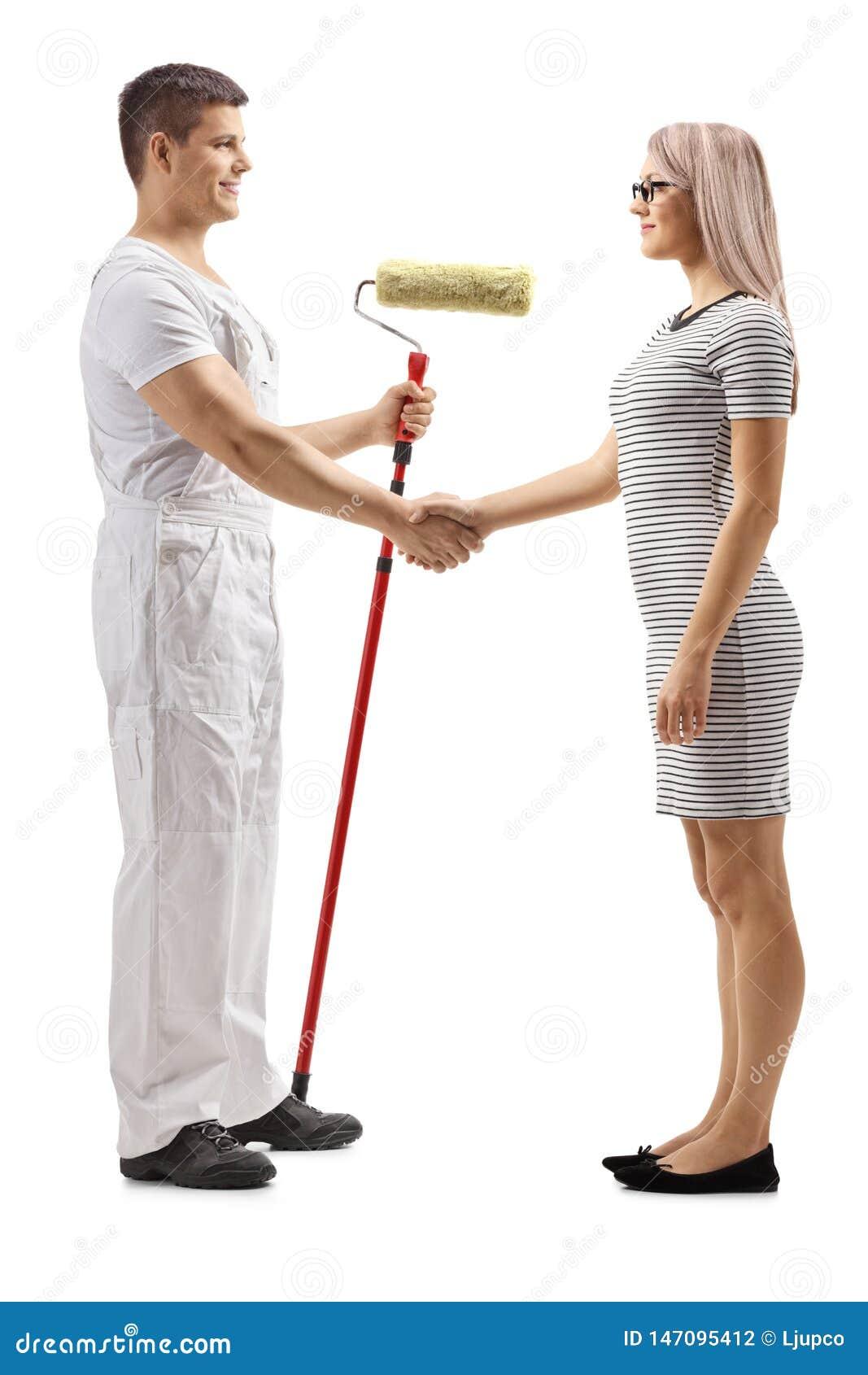Männlicher Dekorateur mit einem Rollenmaler, der Hände mit einer jungen Frau rüttelt