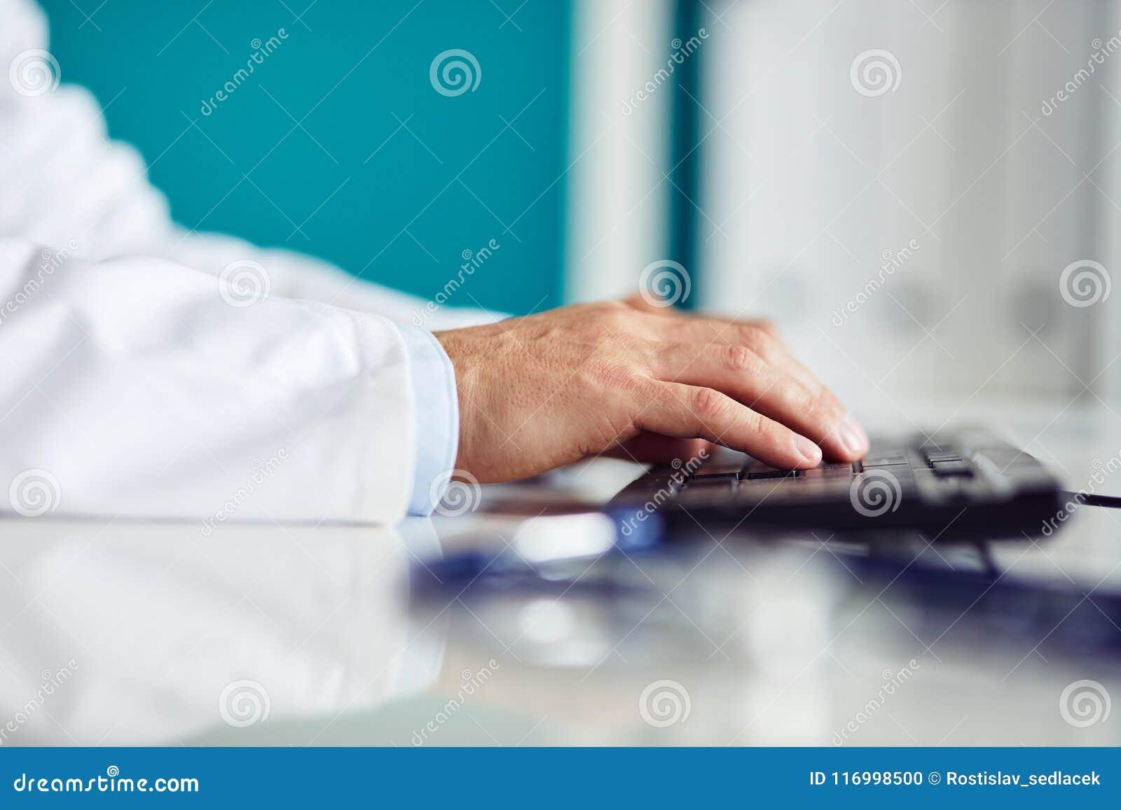 Männlicher Doktor, der auf Tastatur im Büro schreibt