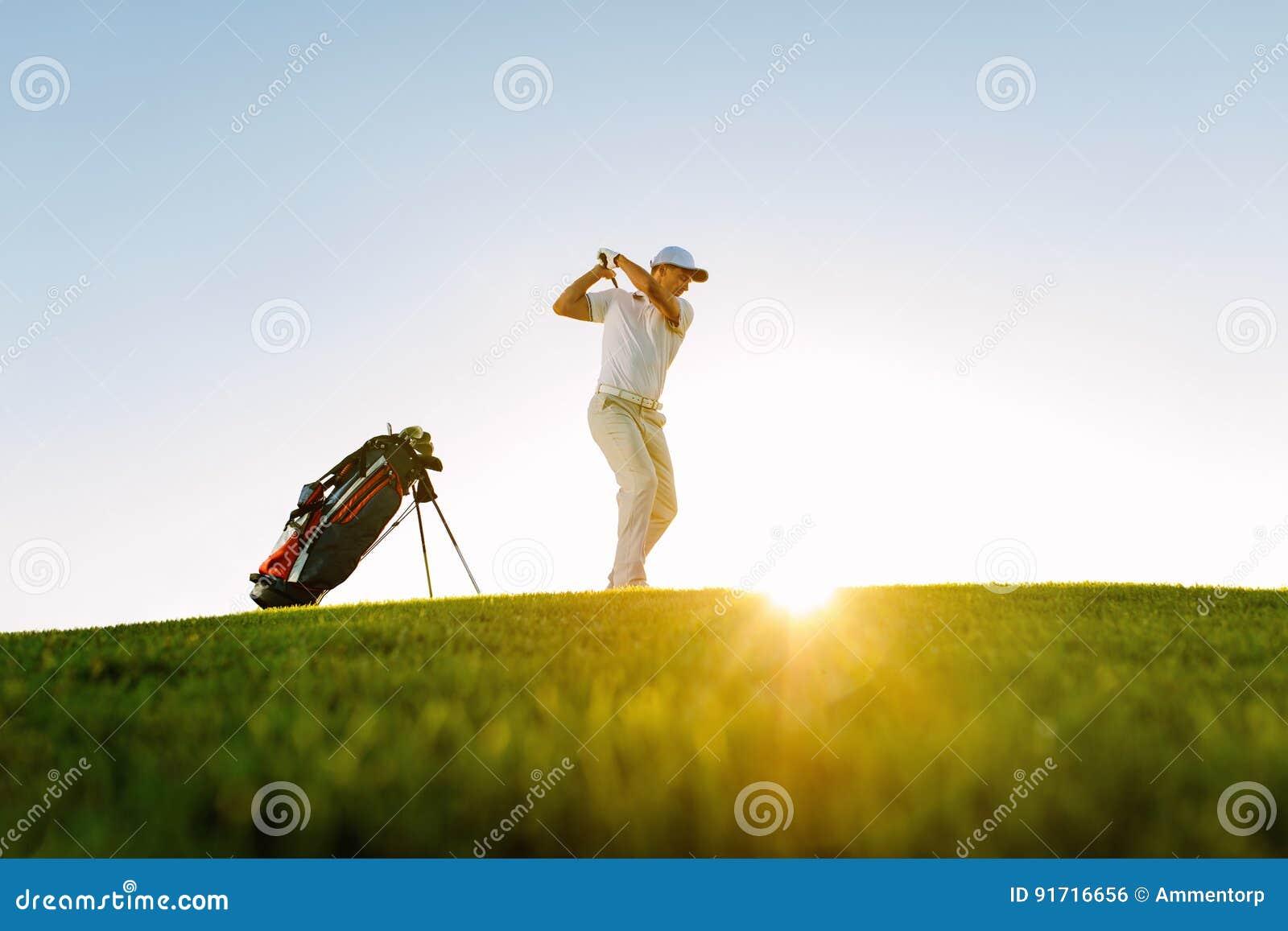 Männlicher Golfspieler, der Schuss auf Golfplatz nimmt