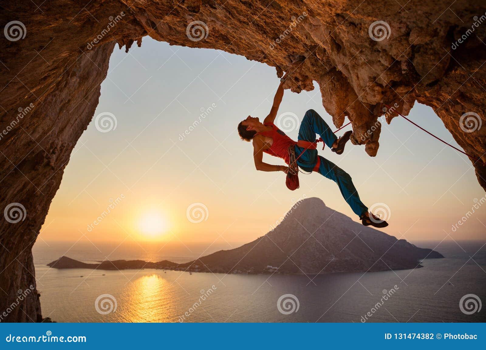 Männlicher Kletterer, der mit einer Hand auf herausforderndem Weg auf Klippe hängt