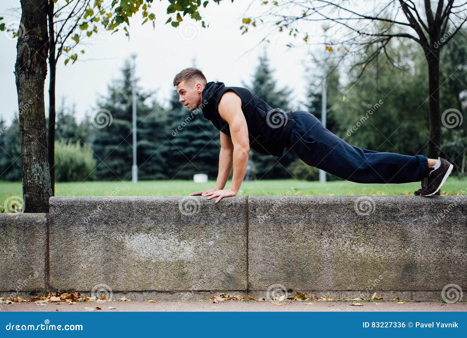 Männlicher Läufer, der Übung, Training im Fallpark tut Drücken Sie ups mit Bank