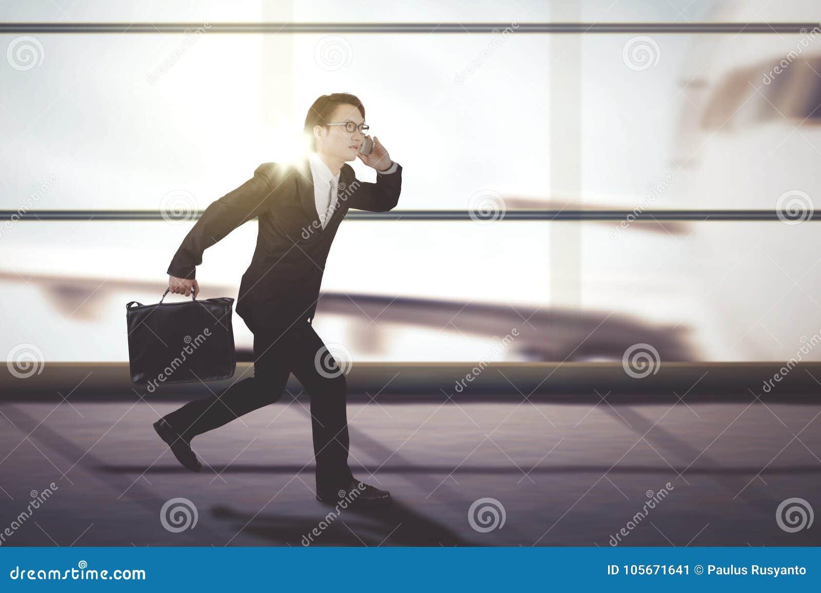 Männlicher Manager, der auf dem Flughafenabfertigungsgebäude läuft