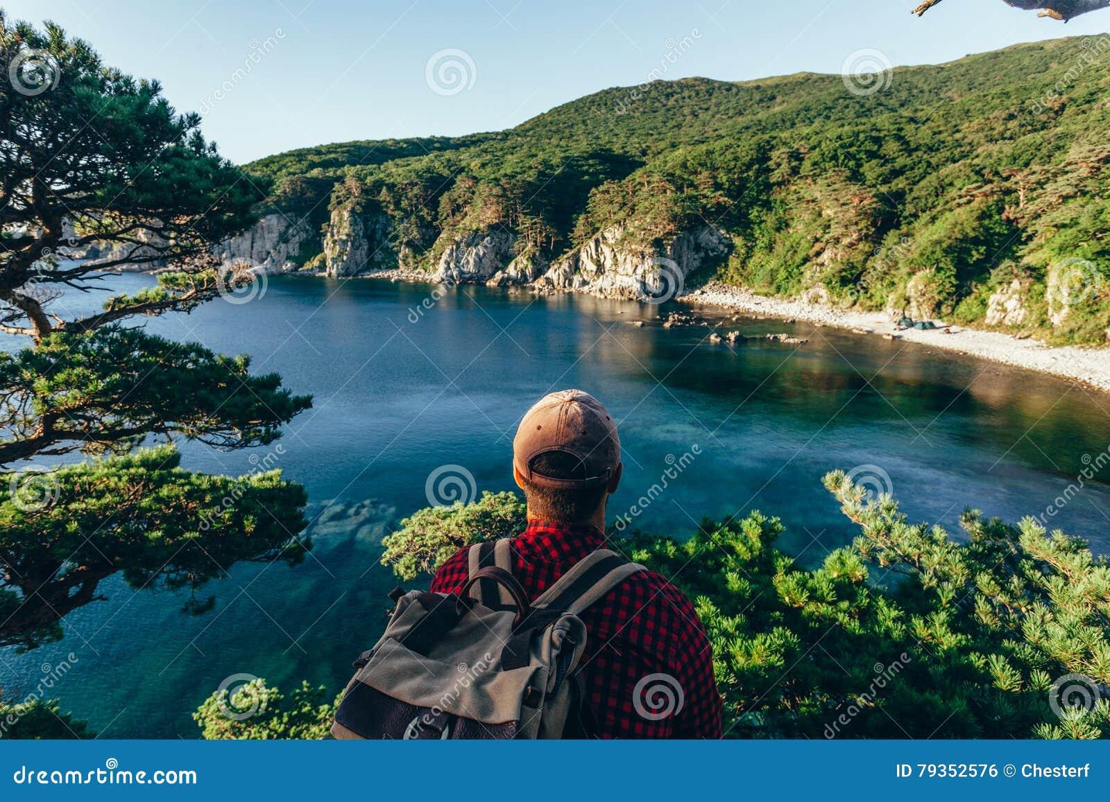 Männlicher Reisender von der Rückseite auf der Seeküste