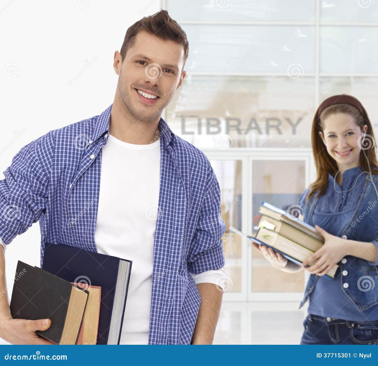Männlicher Student, der Bücher an der Bibliothek hält