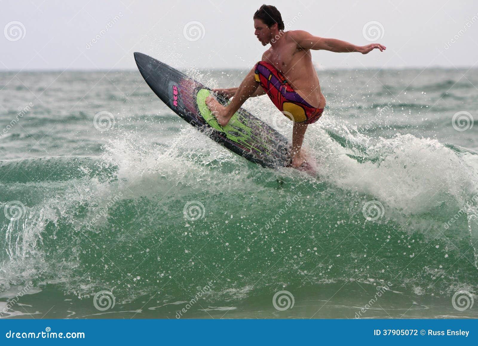 Männlicher Surfer reitet Spitze der Welle weg von Florida-Küstenlinie