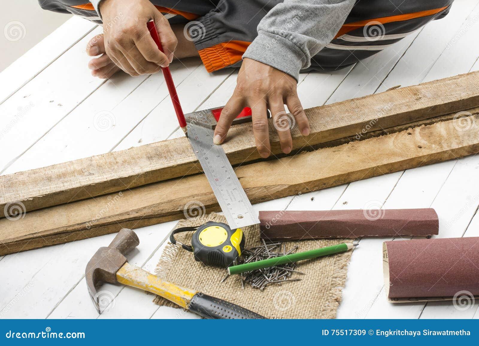 Männlicher Tischler, der mit hölzernem Bleistift und Werkzeugen am Arbeitsplatz arbeitet Hintergrundhandwerkerwerkzeug