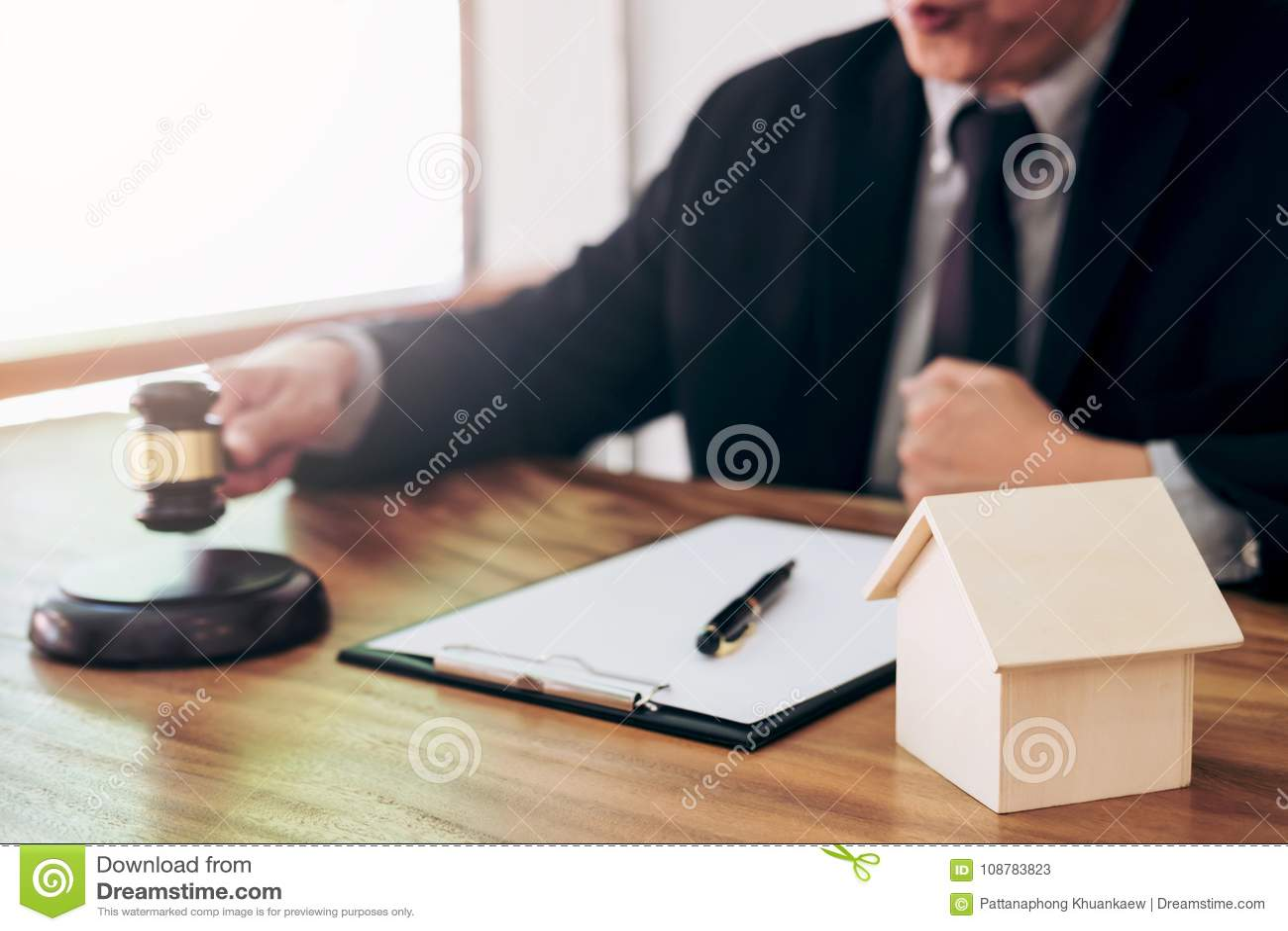 Männliches Rechtsanwalt- oder Richterhand-` s, das den Hammer auf dem Klingen des Blockes schlägt