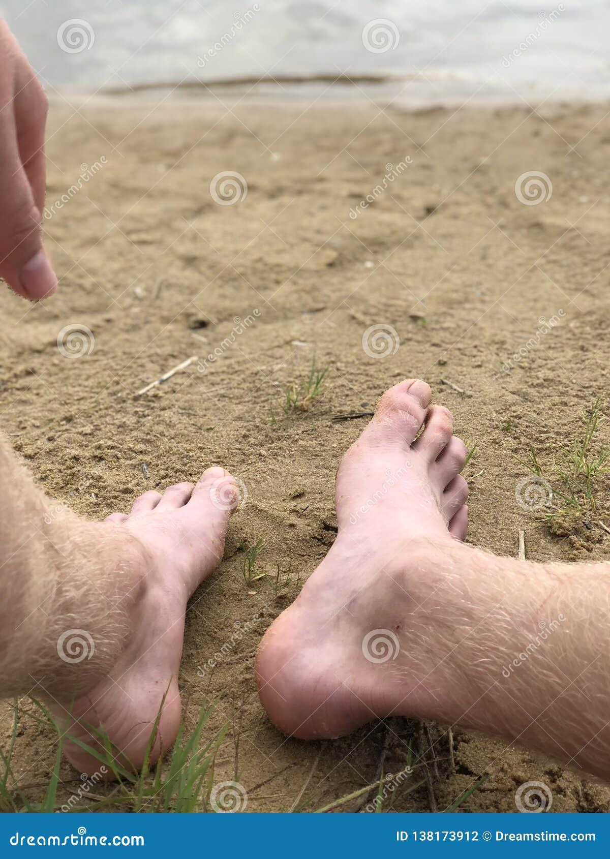 Mäns fot och hand mot sanden och floden