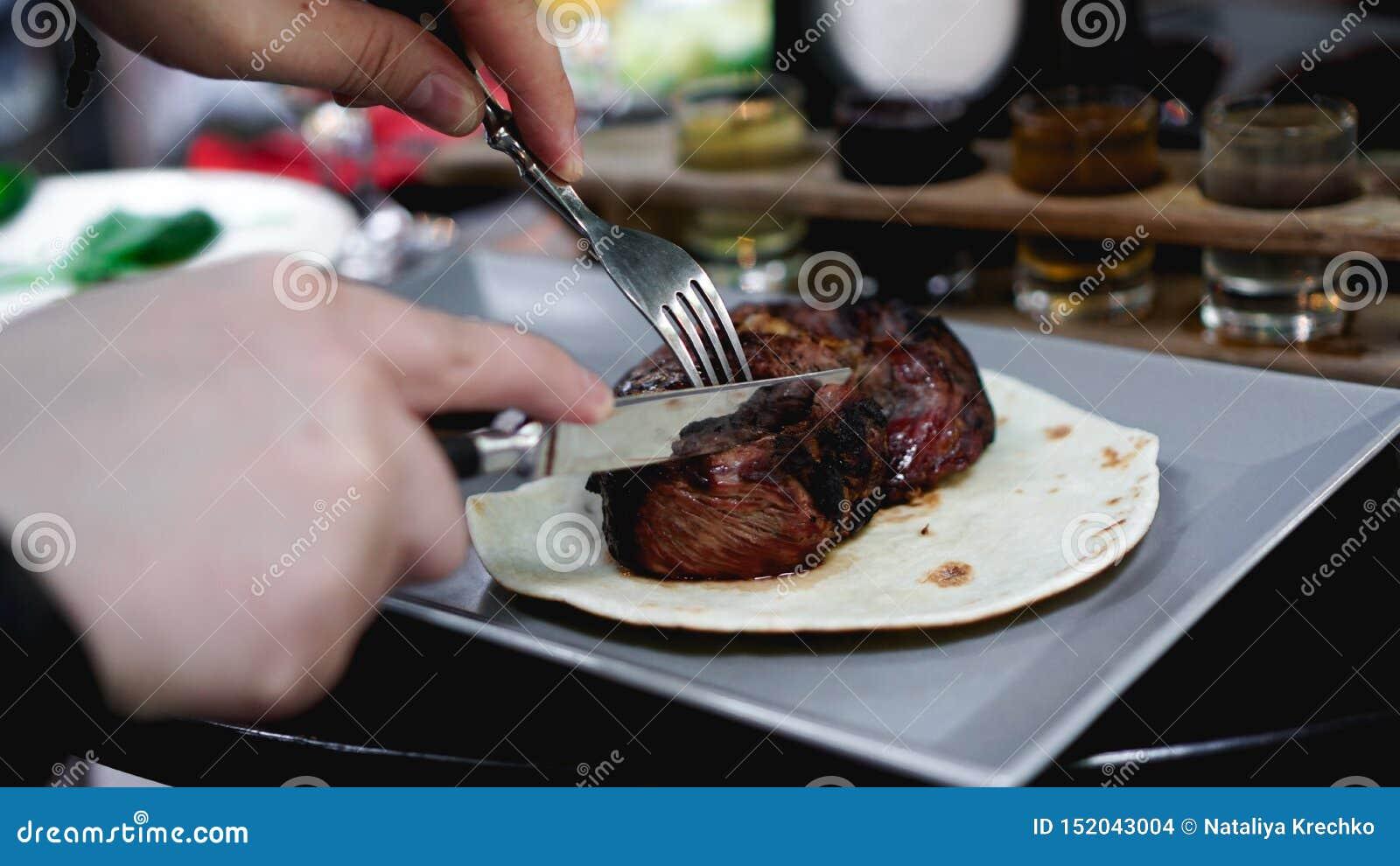 Mäns händer klippte saftiga stycken av kött Han klipper biff på pitabröd