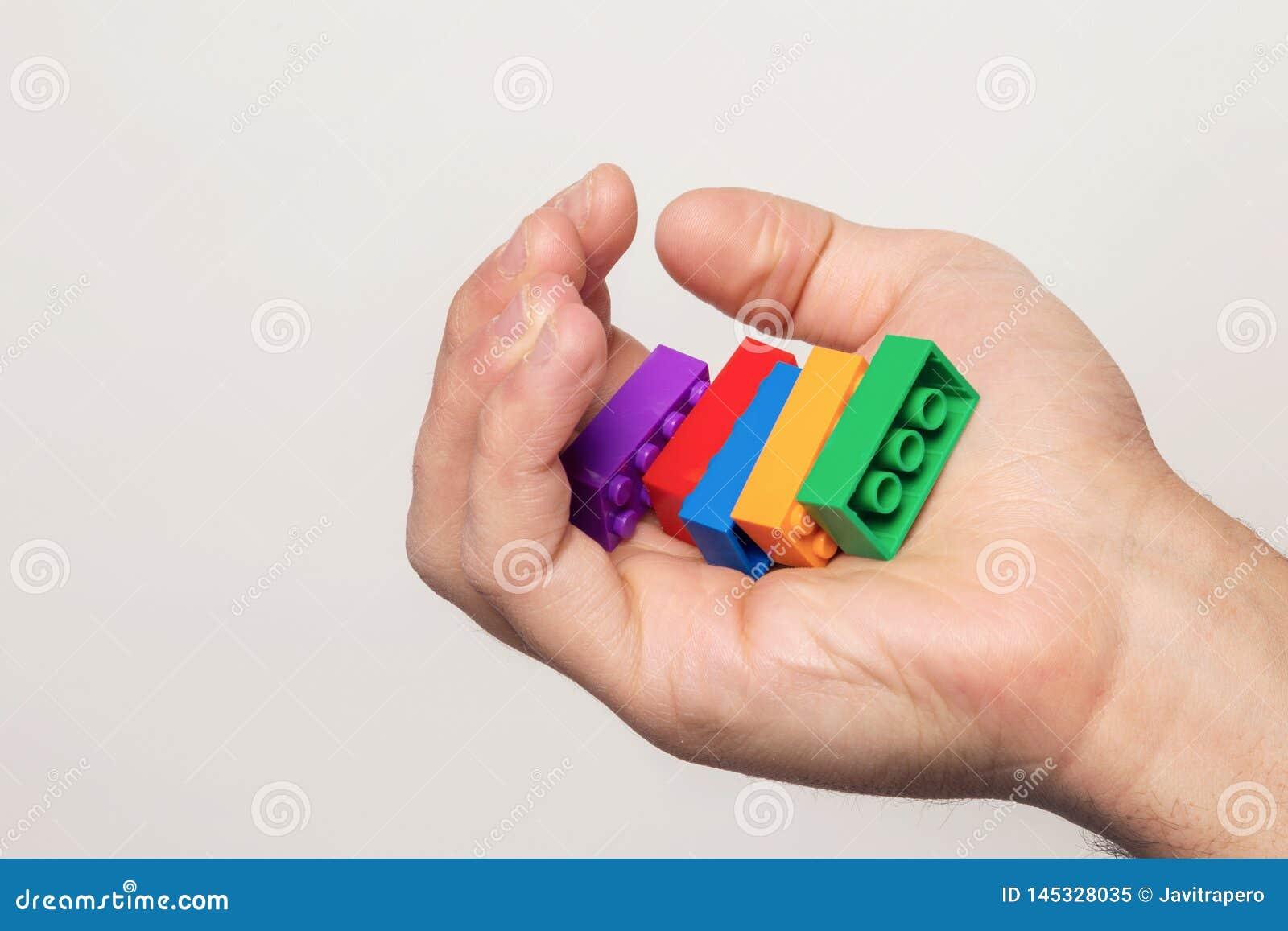 Mänsklig hand med färgglade tegelstenar över en vit vägg